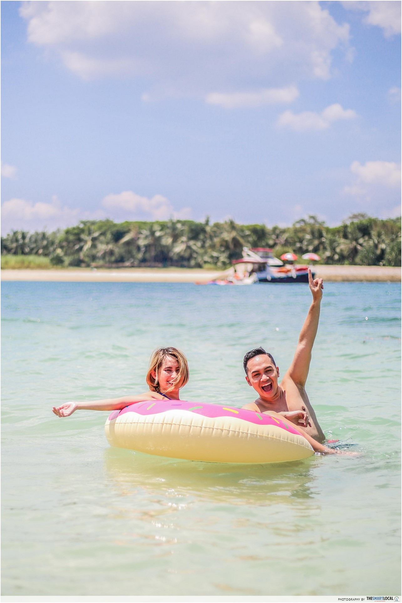 fauzi and beatrice having fun with their float on lazarus island beach