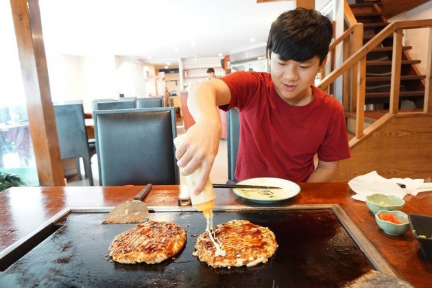 man making okonomiyaki at Nanjya Monjya japanese restaurant