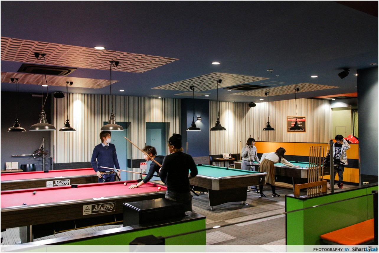 The Smart Local - Several people playing billiards and pool in the arcade
