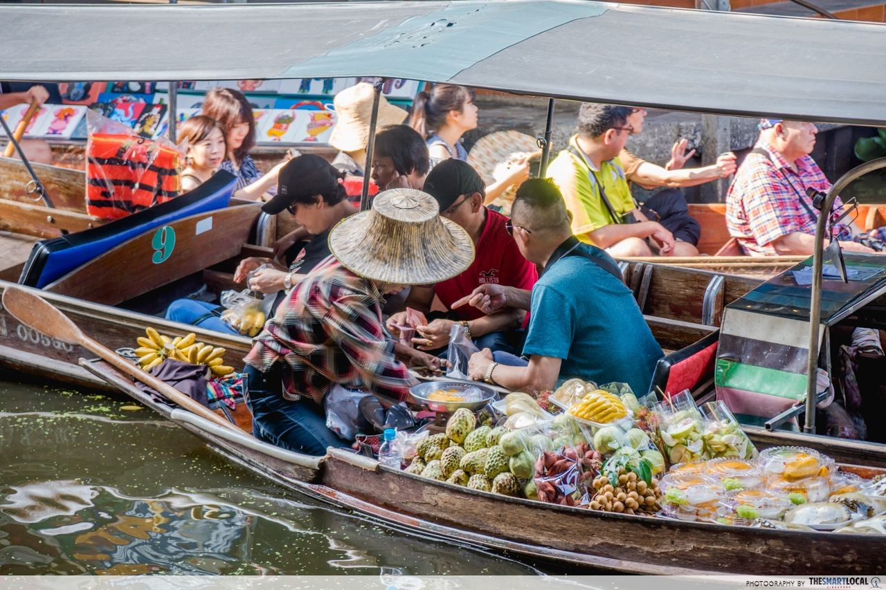 Tourists buying food from their rowboats