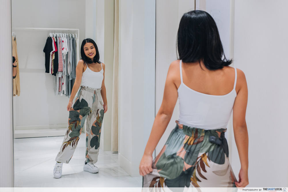 Girl trying on leaf motif pants at Oysho