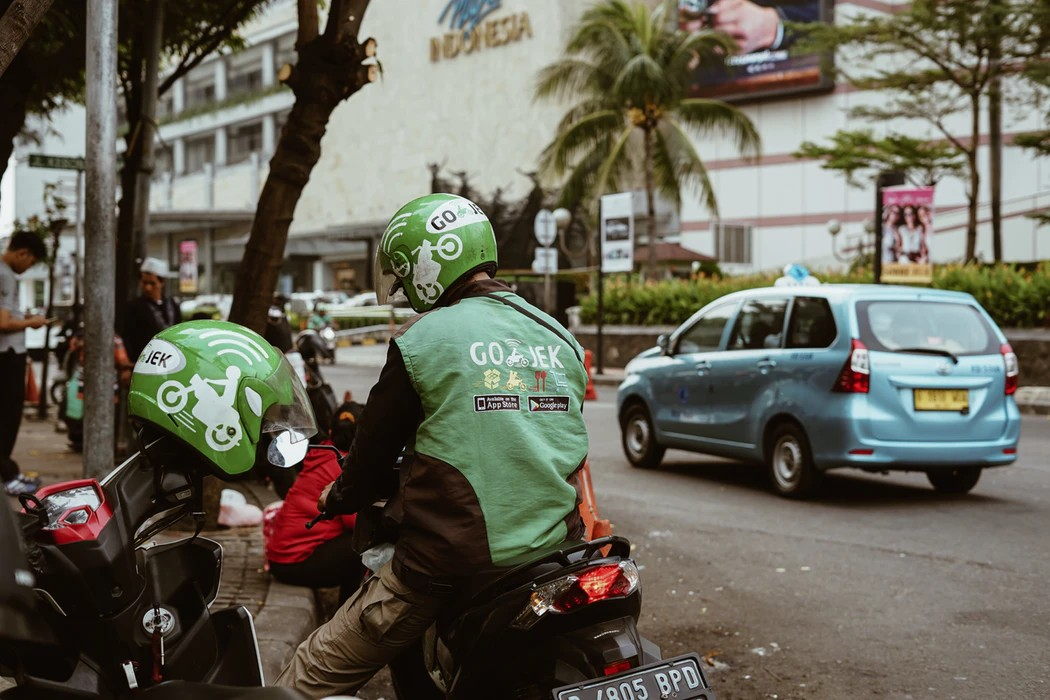 ojek driver waiting on side of the street