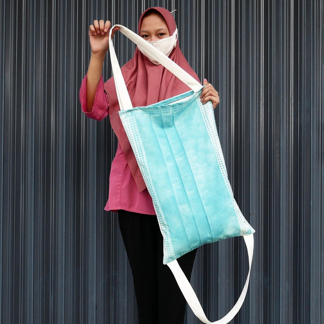 Woman showing off a surgical face mask tote bag