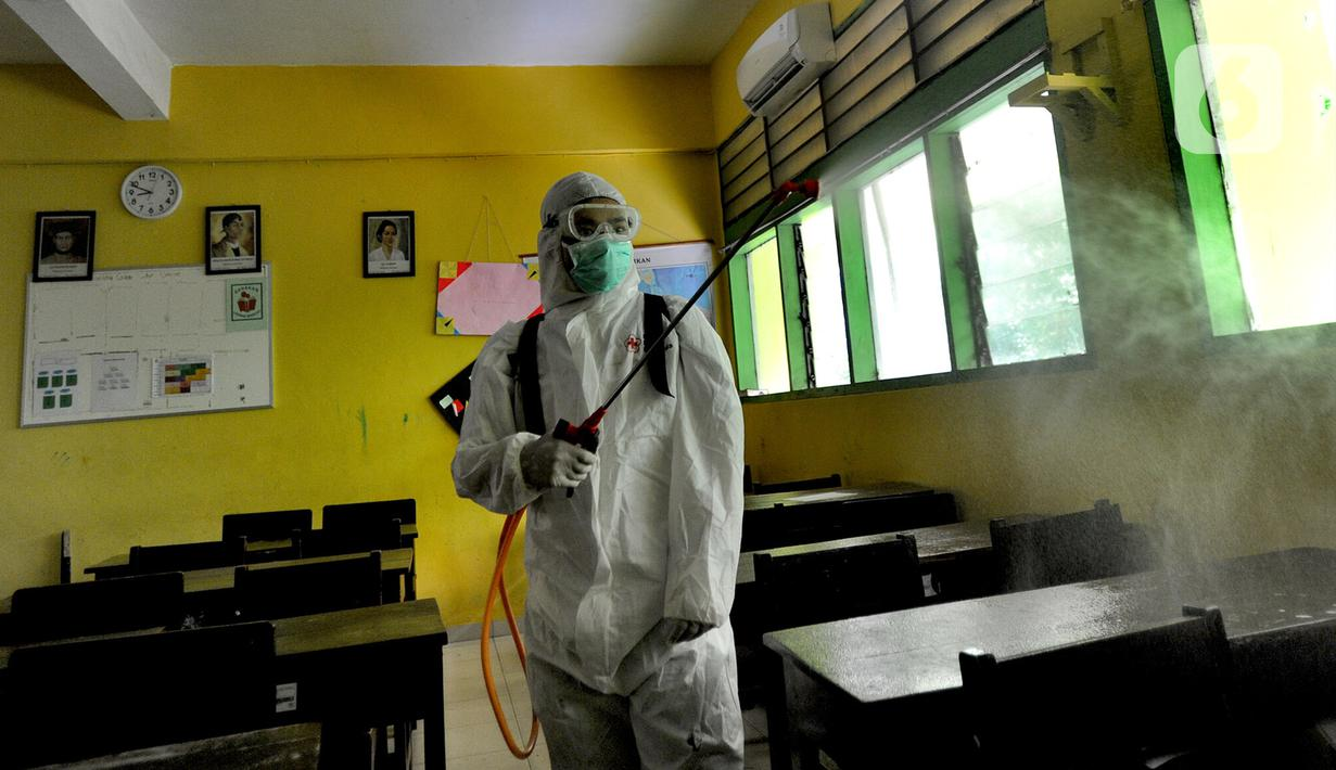 A person disinfects an empty classrom