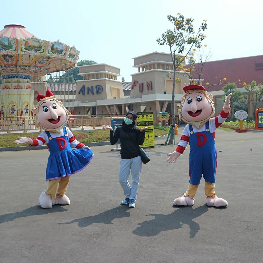 Visitor wears face mask, poses with Dufan mascots