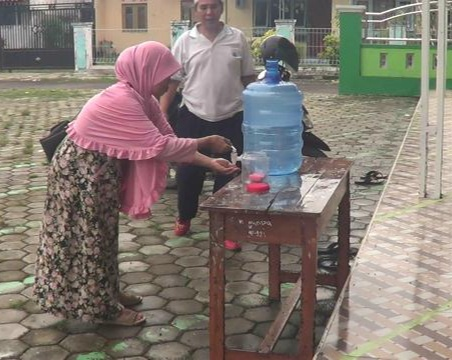 Health protocol breakers could face sanctions - Woman washing hands in Tegal