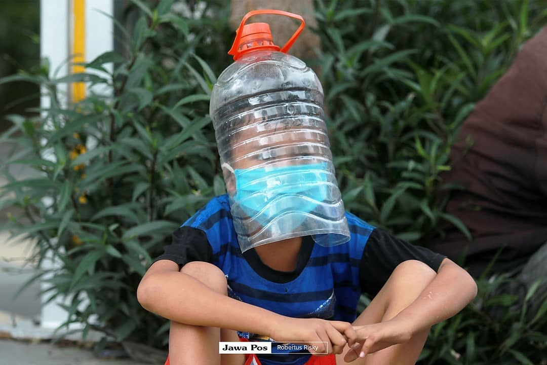 Indonesians' DIY PPE - Child wearing water jug