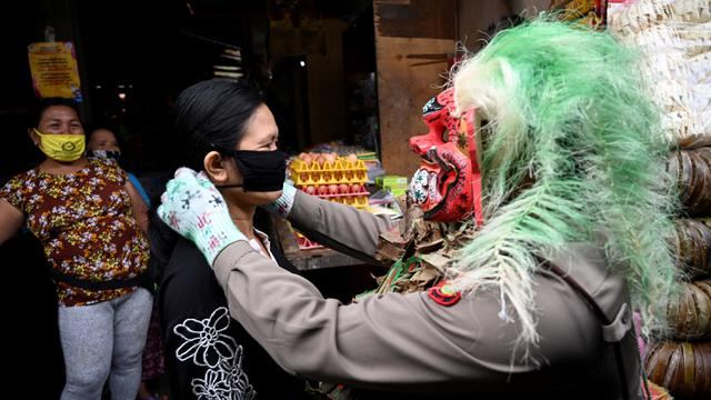 Bali face mask fines - Policeman puts a mask on a woman