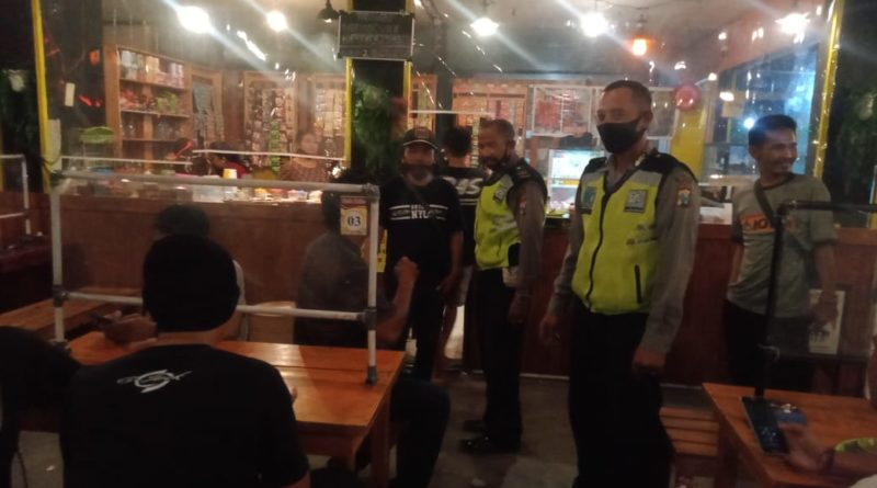 gresik police conducting night patrol at restaurant during pandemic