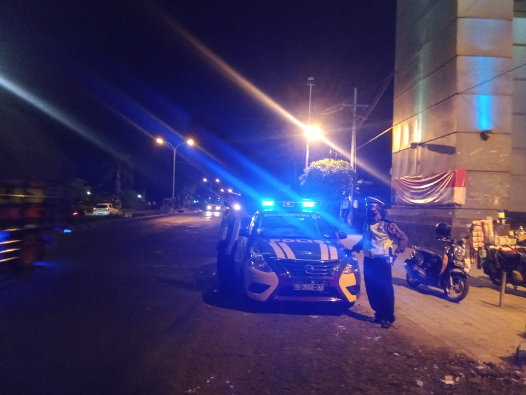 gresik police conducting night patrol on roadside during pandemic