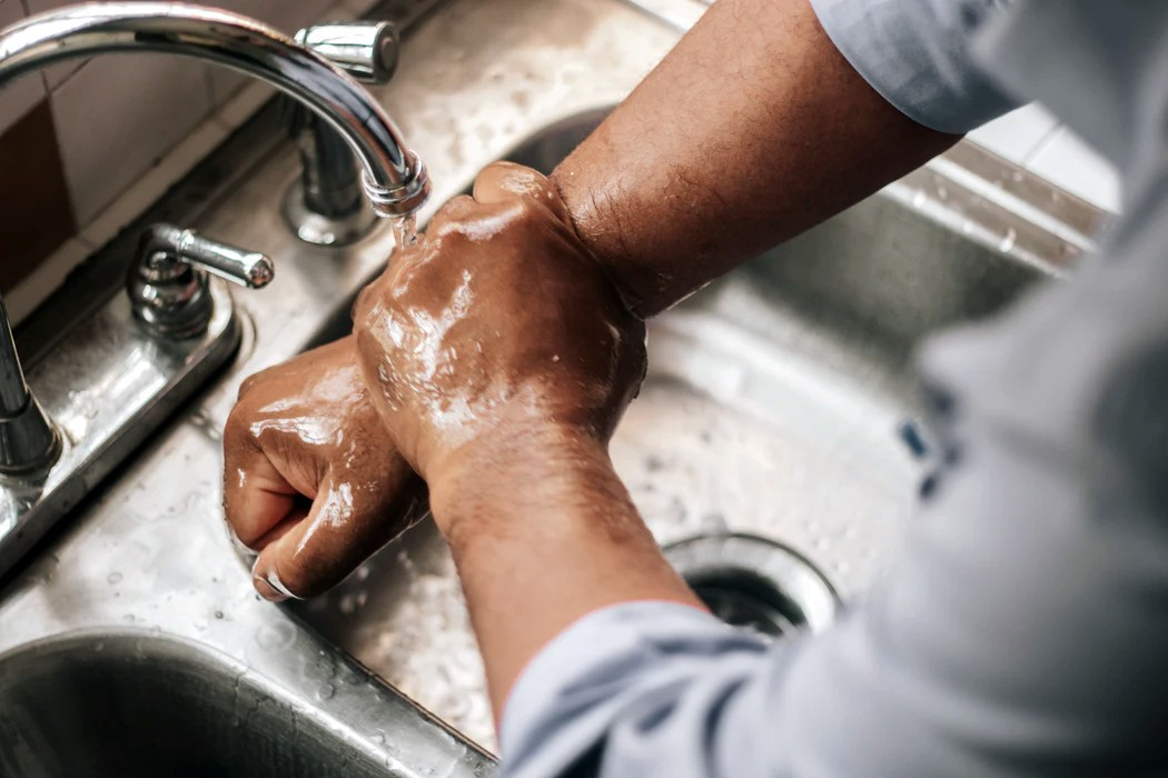man washing his hands in a sink