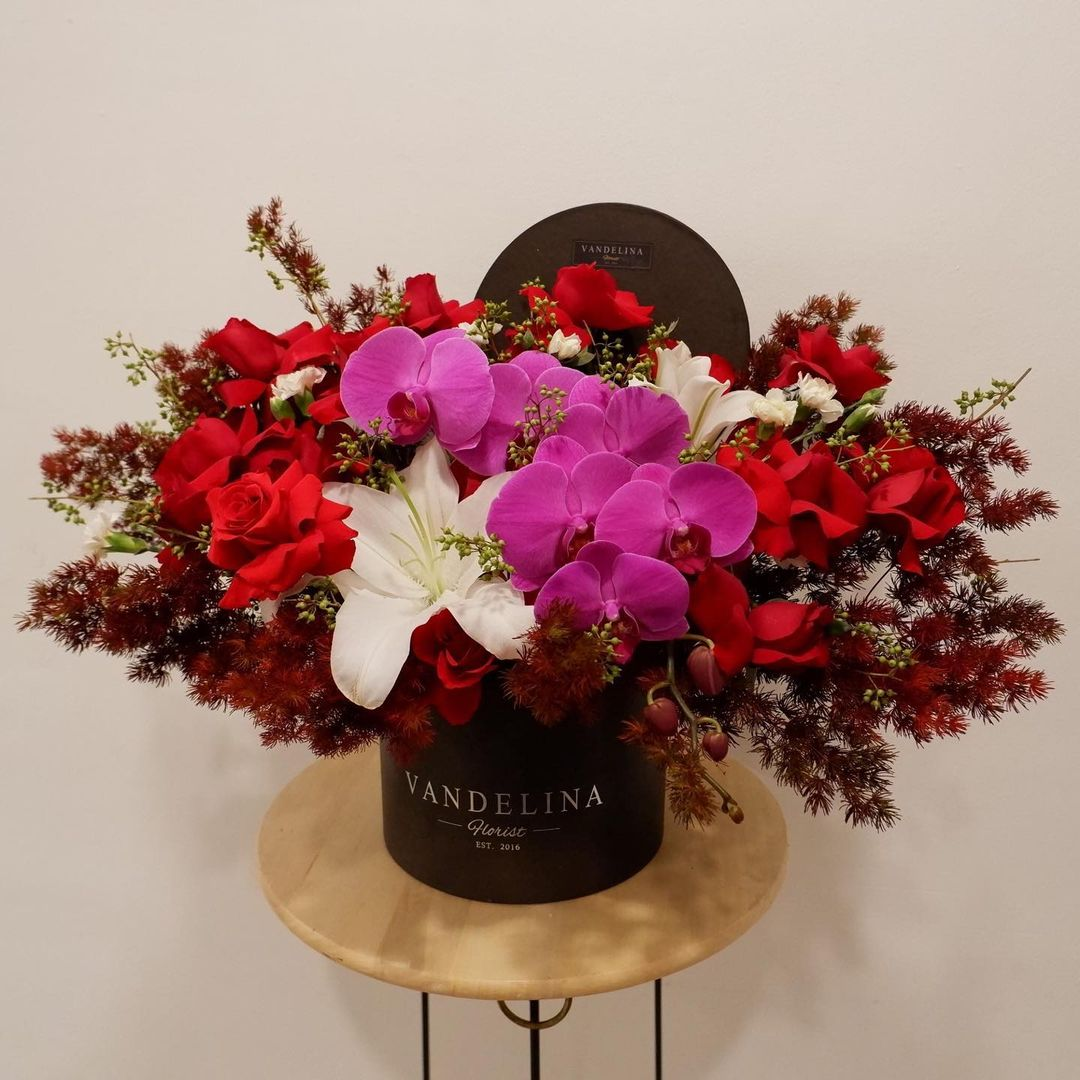 roses and orchids in a bloom box