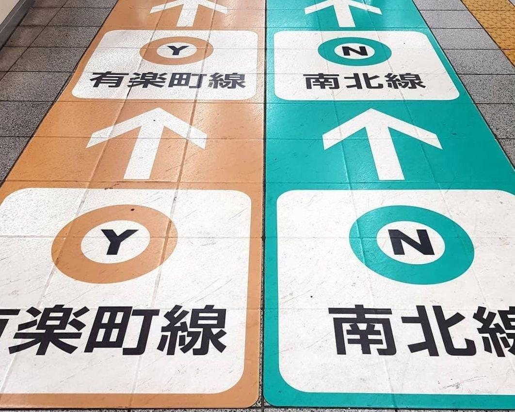 Colour-coded arrows on the floor in a Tokyo train station