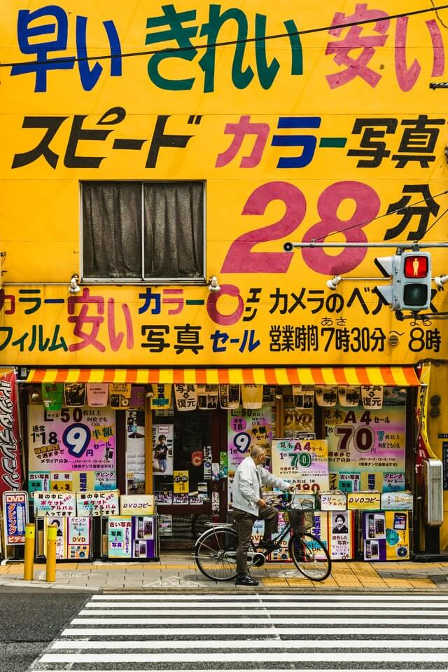 Useful Japanese tips - man waiting to cross the road outside a drug store in Japan