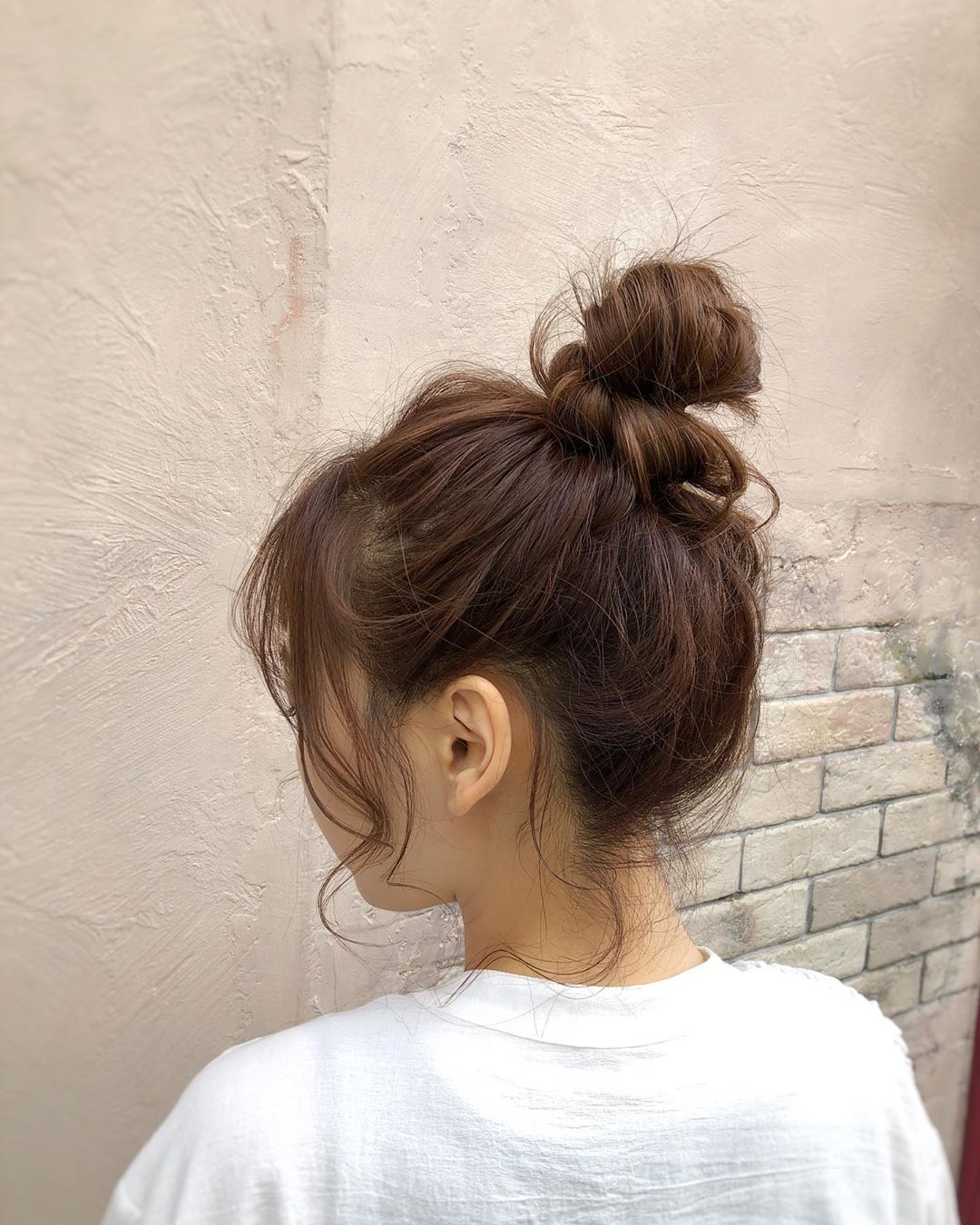 japanese hairstyles - textured messy bun with long side fringe back view