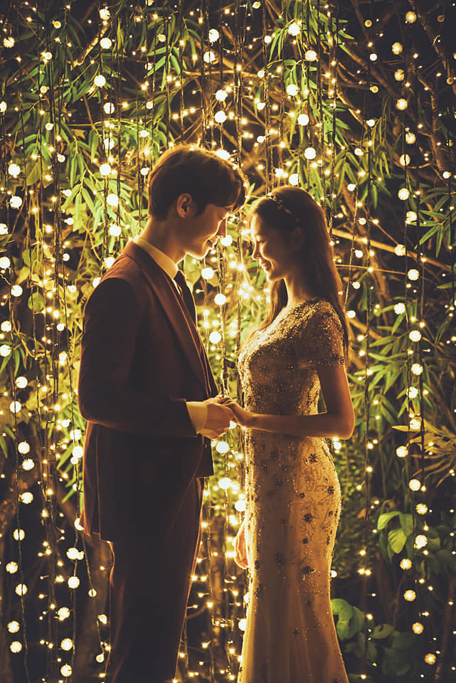 korean wedding photoshoot with fairy lights in the background