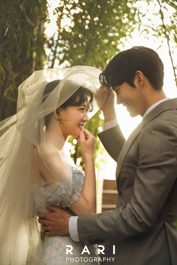 korean wedding photoshoot groom removing bride's veil