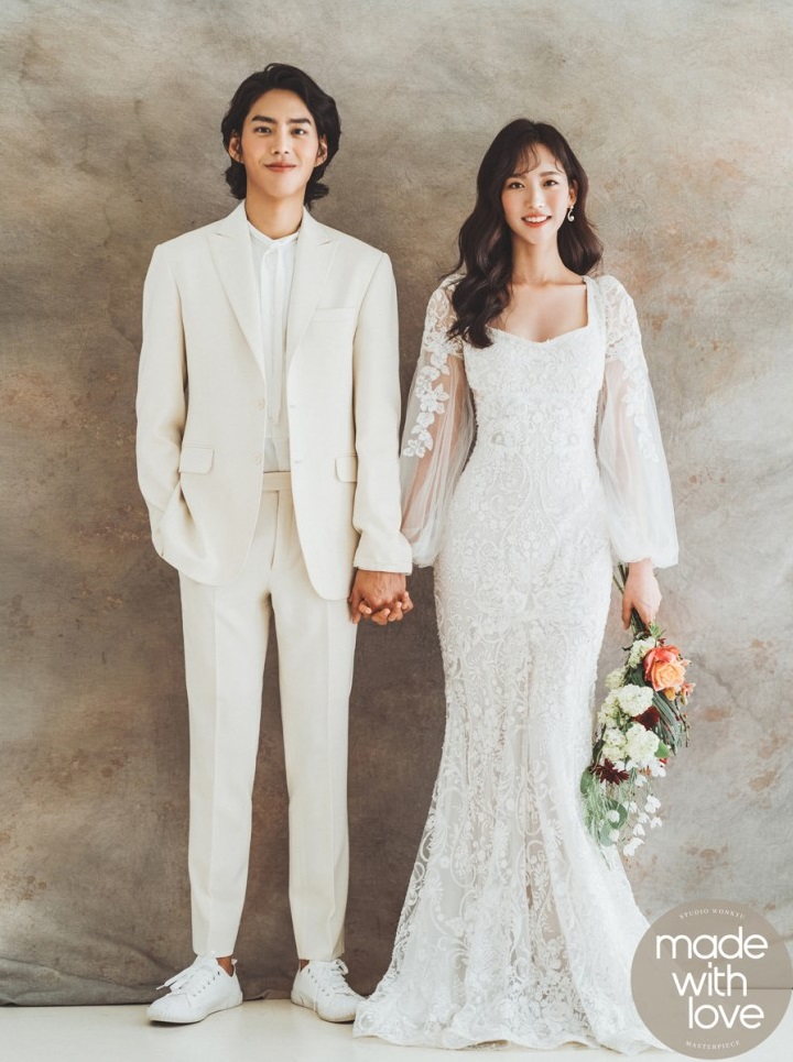 korean wedding photoshoot couple dressed in all white against a wall