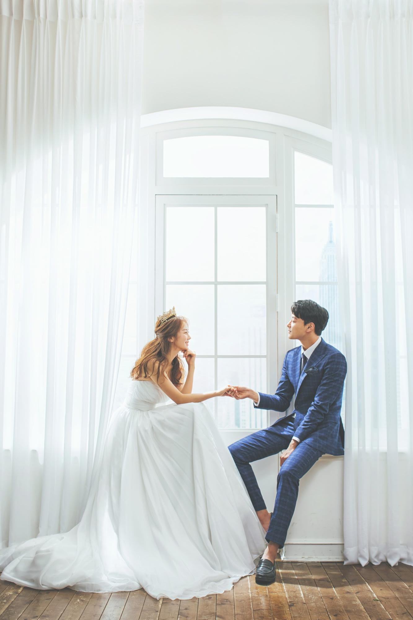 korean wedding photoshoot couple sitting by a white window sill