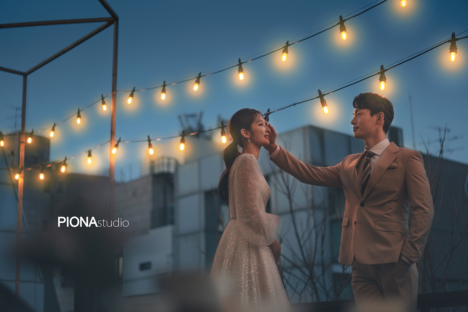 korean wedding photoshoot suspended lightbulbs over couple