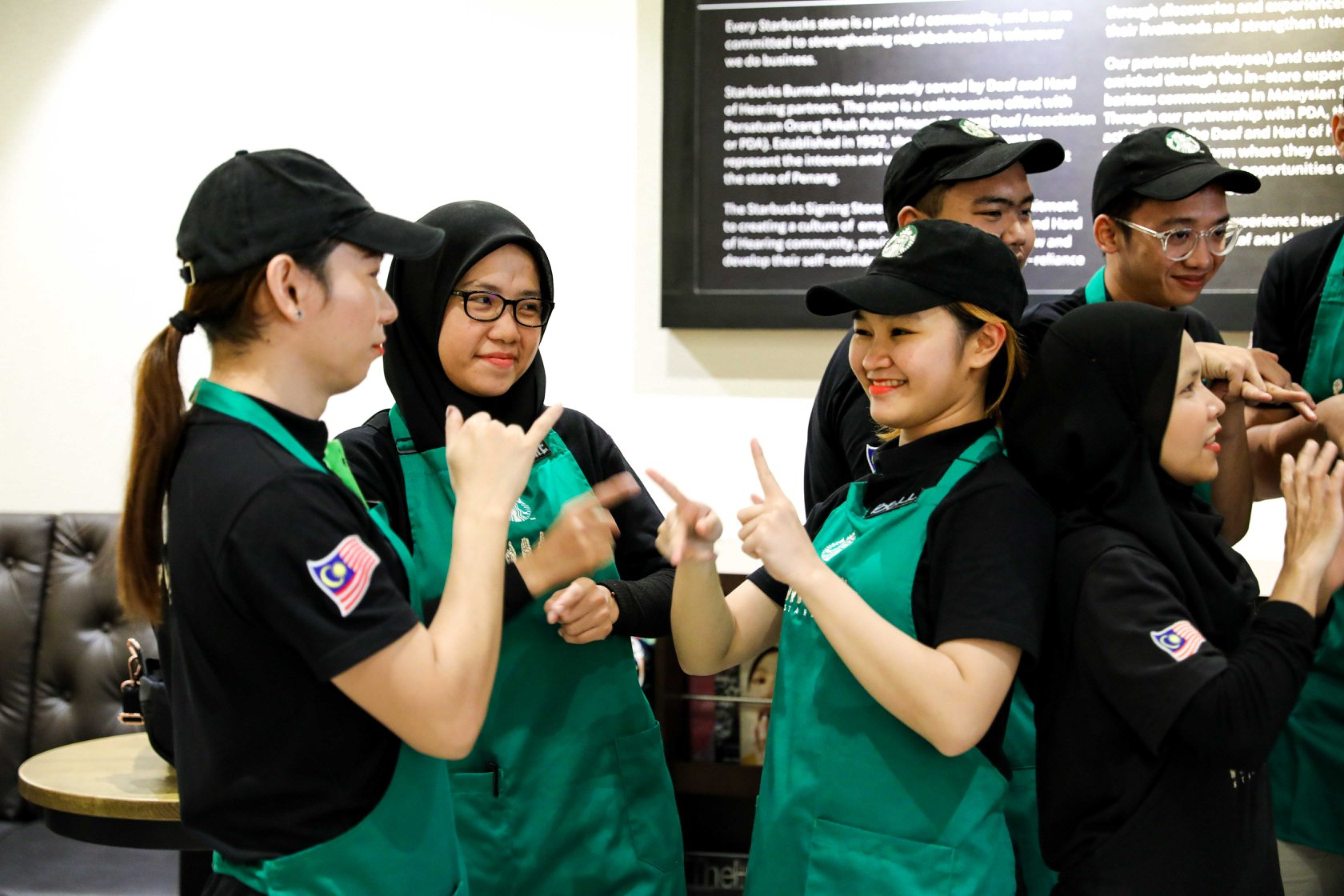 Starbucks staff signing each other