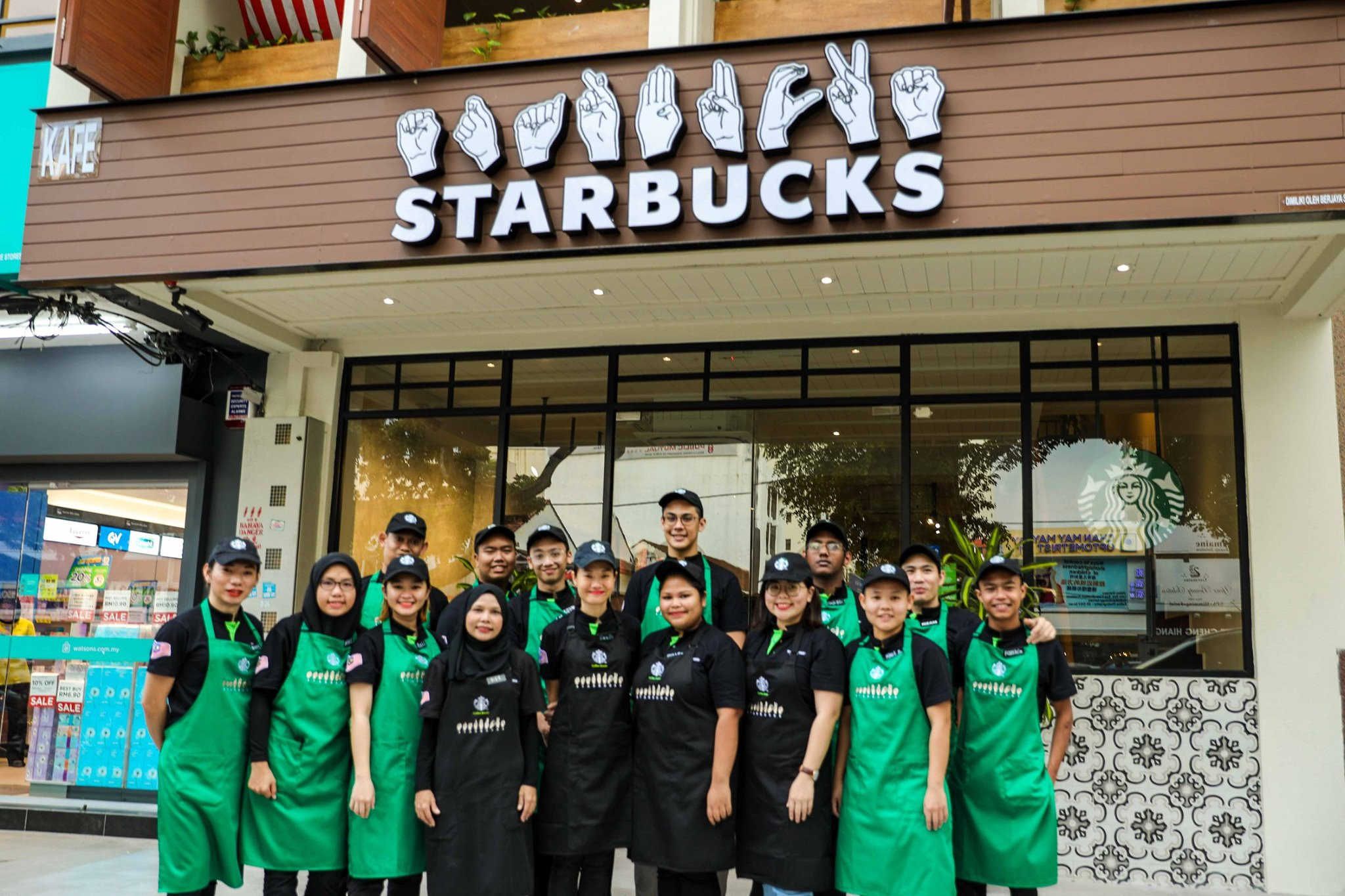 Starbucks staff posing outside the store