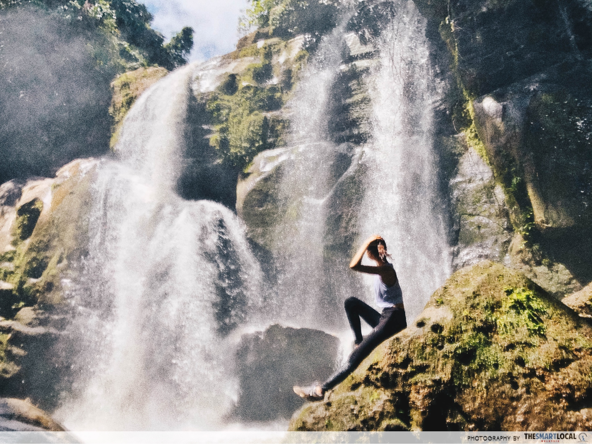 author posing in front of a waterfall
