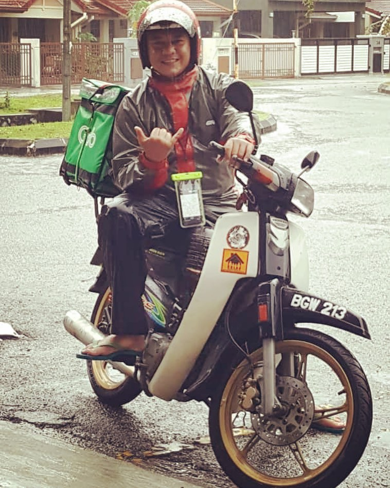 food delivery rider posing on his bike