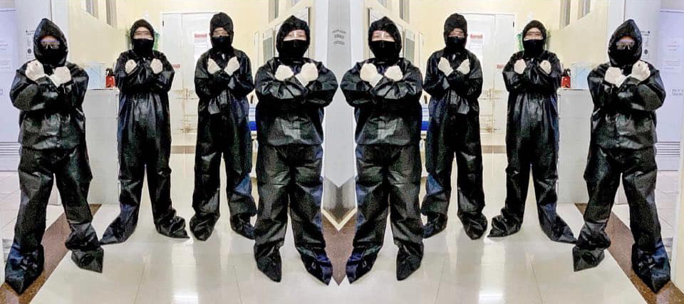 men in black hazmat suits, with their fists across the chest