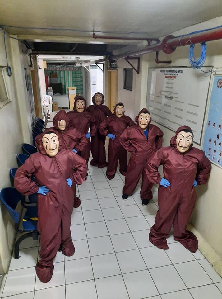 health workers in maroon hazmat suits and Salvador Dali masks