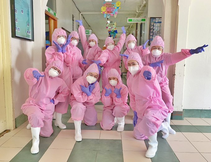 health workers in pink hazmat suits and purple gloves