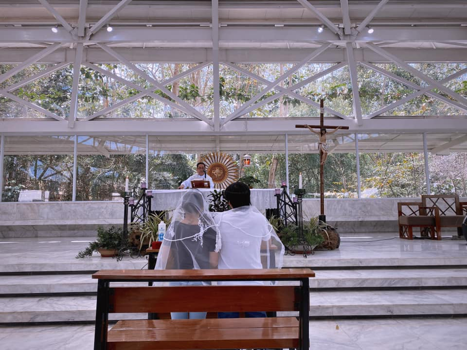 bride and groom in shirts and jeans, in front of priest