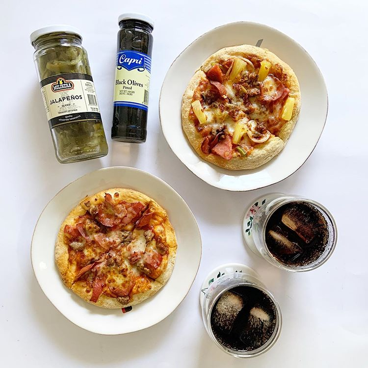 two small pizzas, two bottles of spices, and two glasses of soda