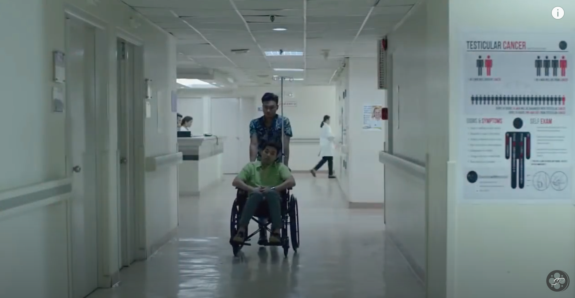 guy pushing another guy in a wheel chair in a hospital