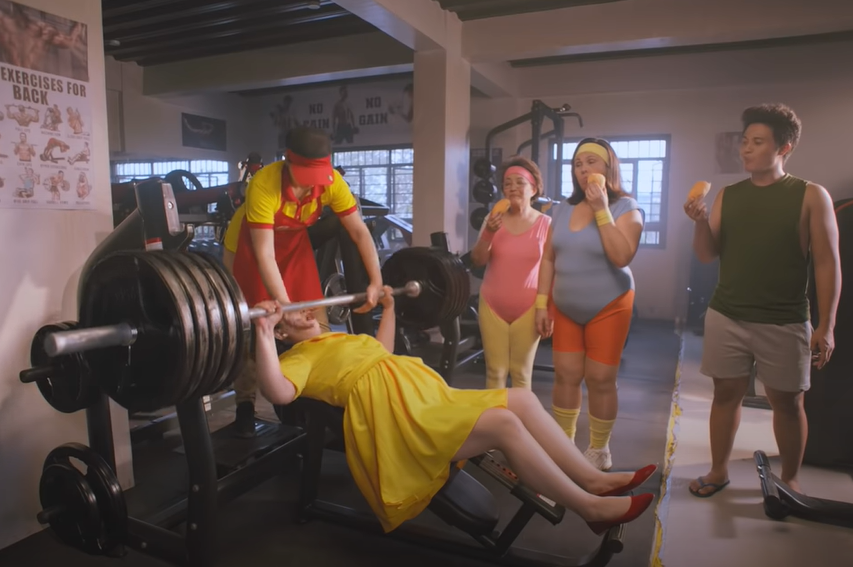 Julie's Bakeshop ad - Tita Julie weightlifting while the gym members eat the newly baked pandesal