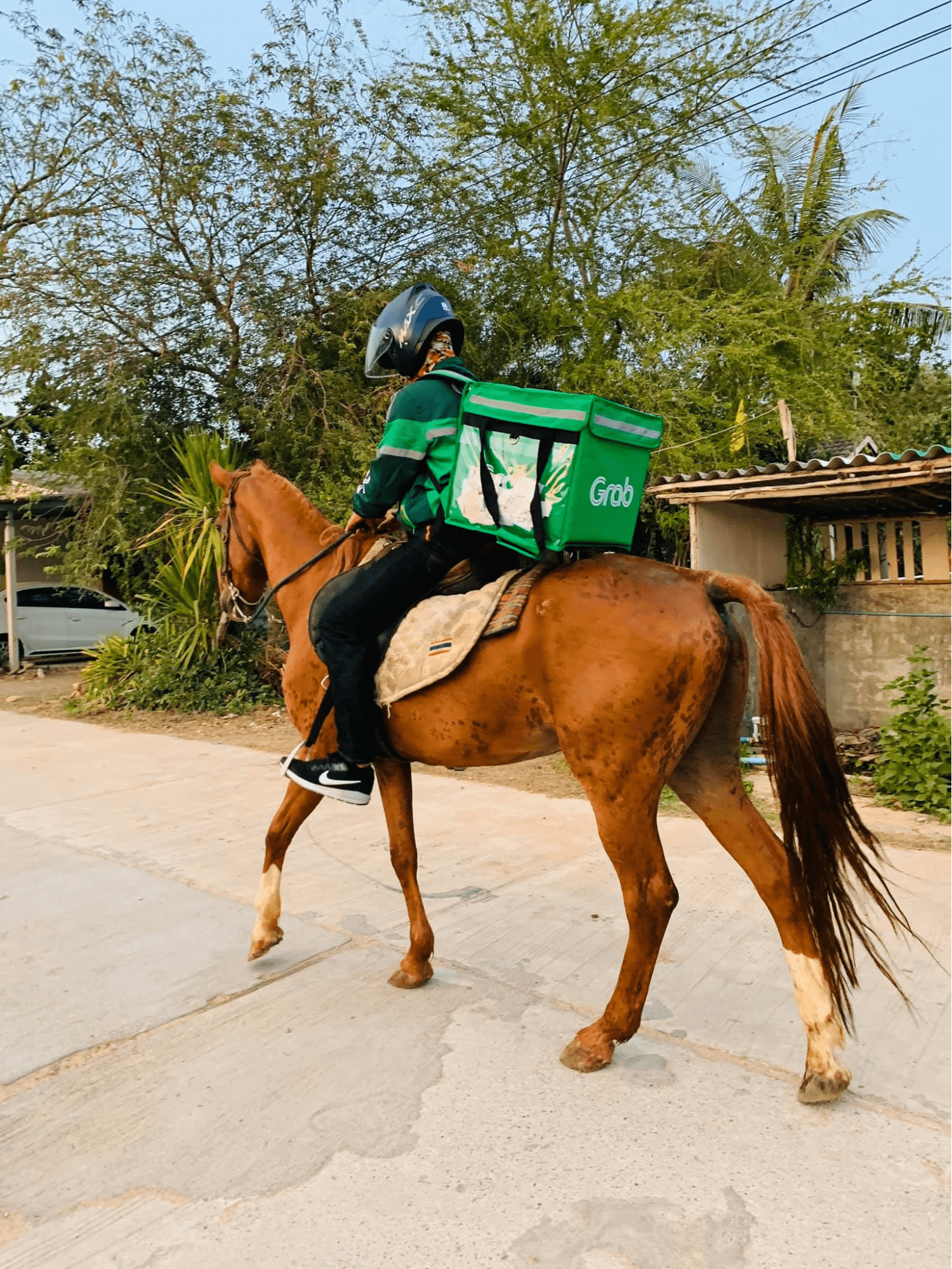 Thai GrabFood delivery man rides a horse