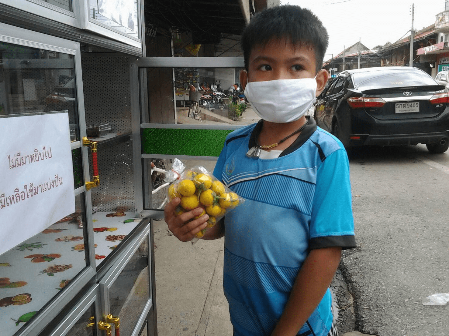 Thai boy bring vegetables to a sharing pantry