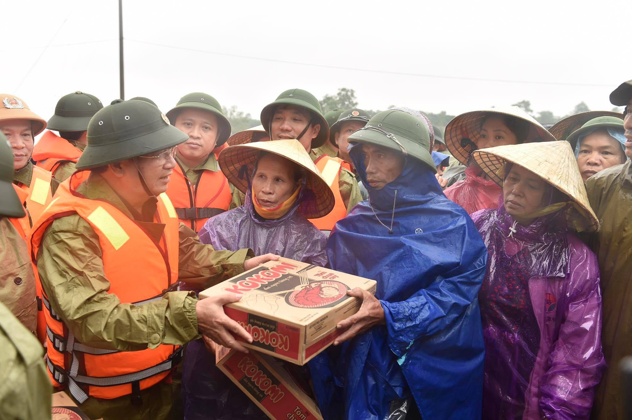 government officials giving food to victims of Central Vietnam floods