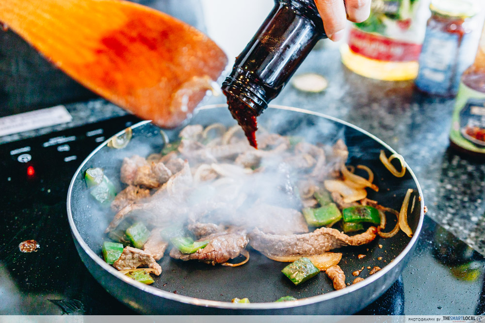 pouring black pepper sauce into pan