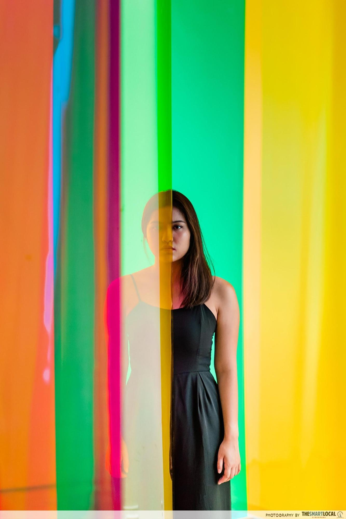 model standing between translucent colored sheets