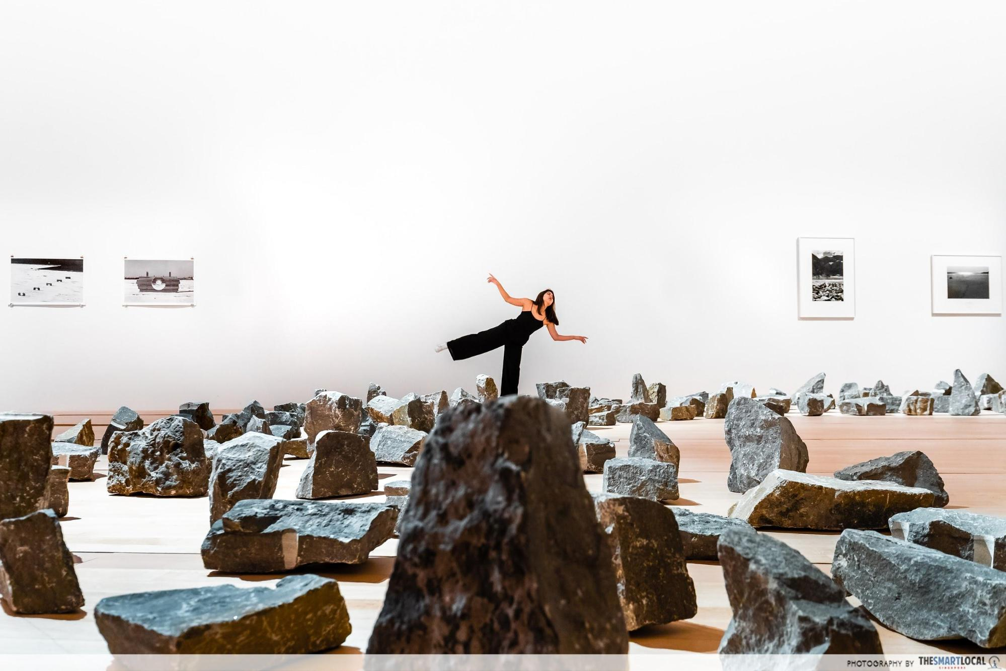 perspective shot of model balancing on rocks