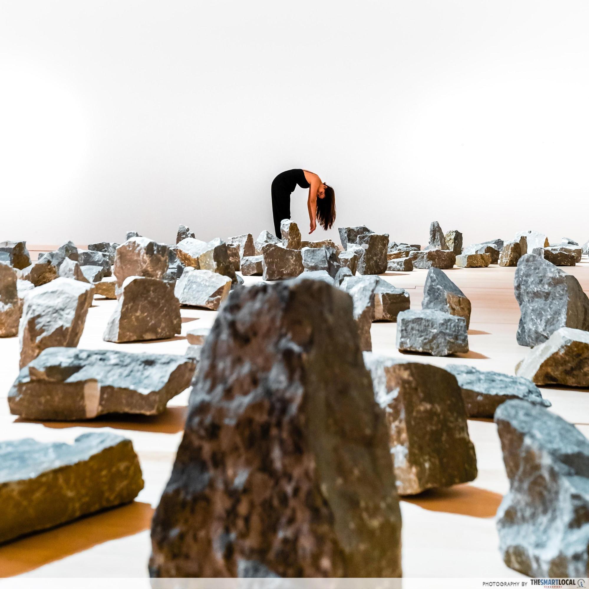 perspective shot of model bending over rocks