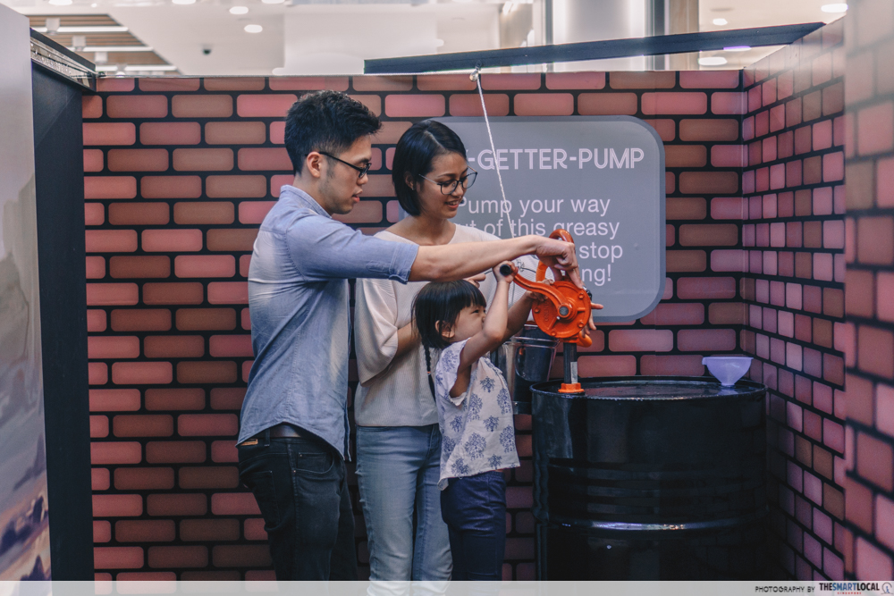 Father, mother and daughter doing pumping oil activity