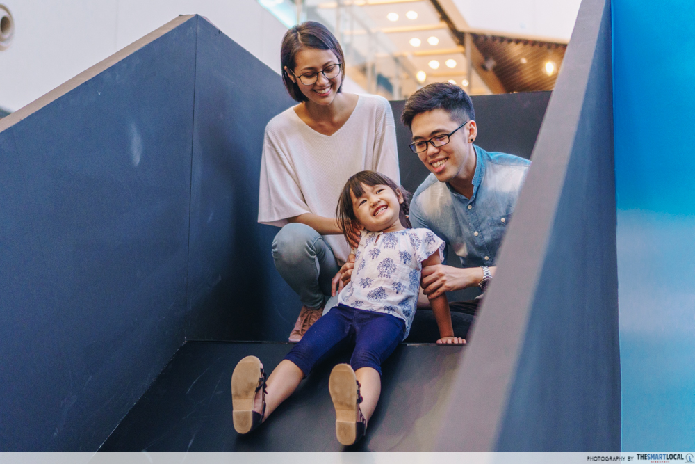 Mother, father and daughter going down slide