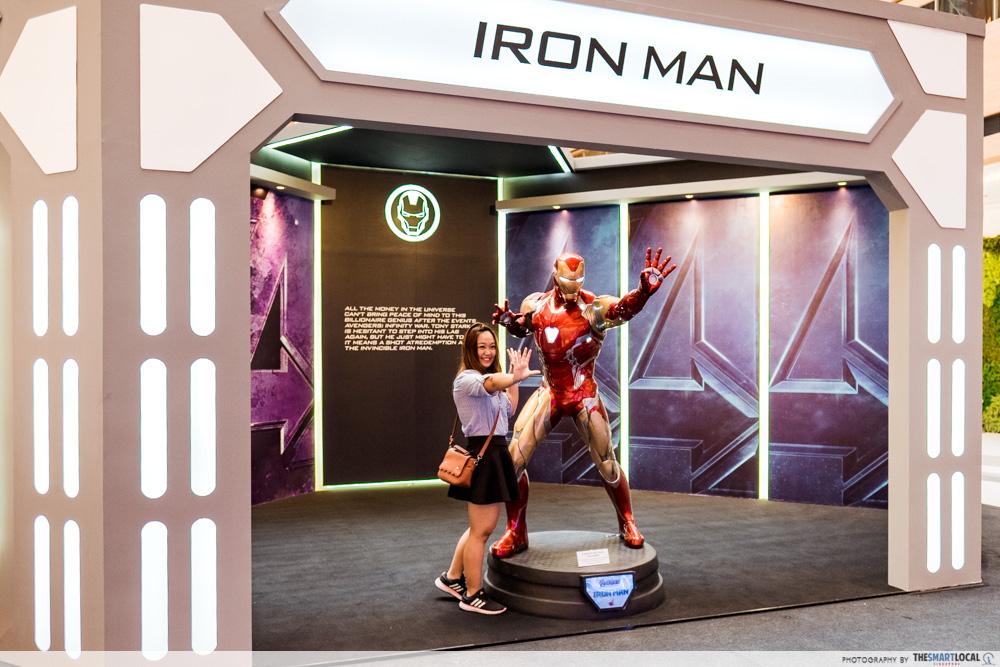 Girl posing with life-size iron man figurine