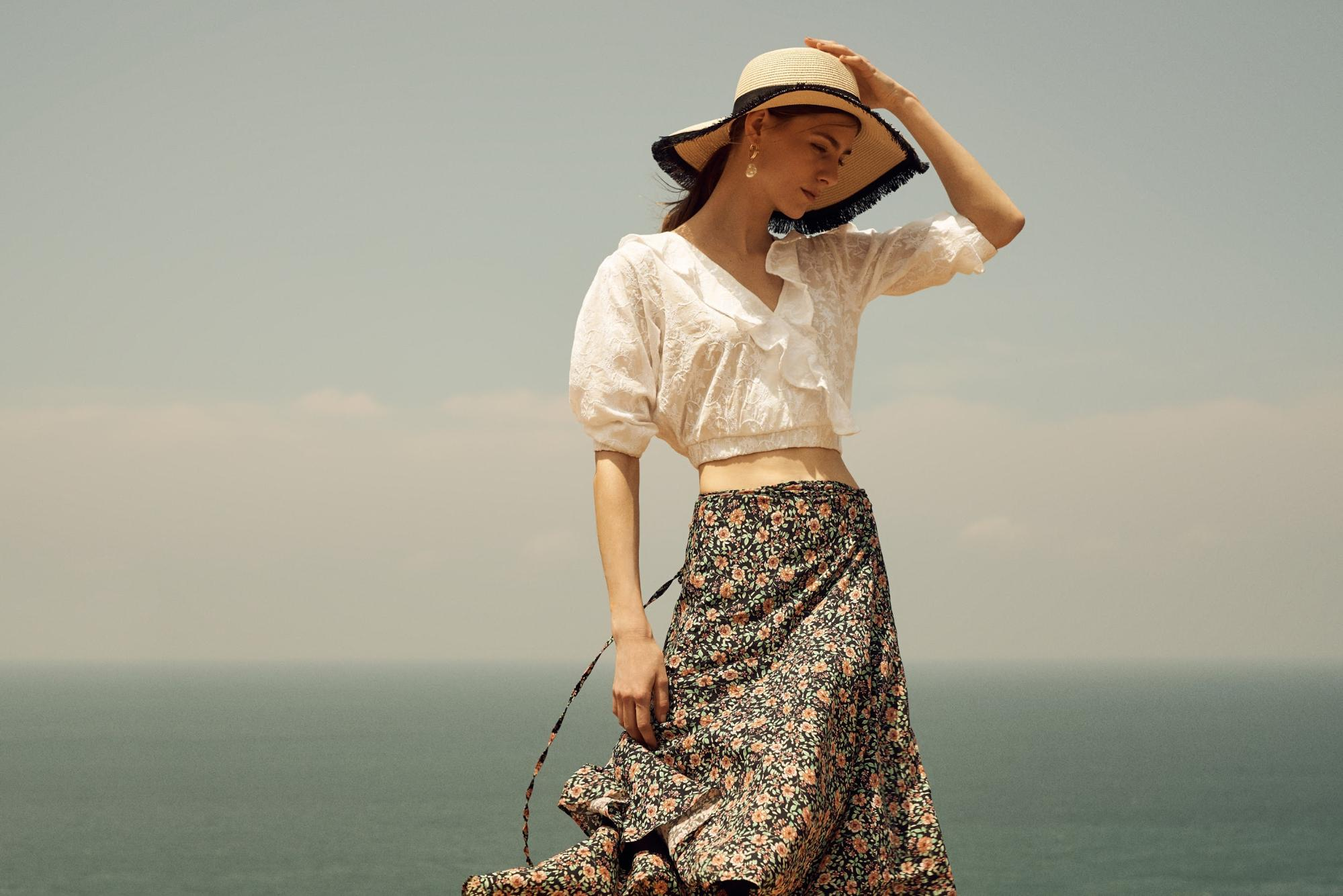 Lady in sun hat at a breezy beach