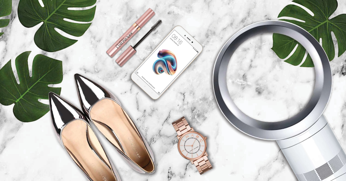 Flatlay of shoes, mascara, phone, watch and fan