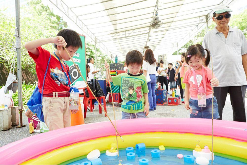 Kids playing fishing carnival game