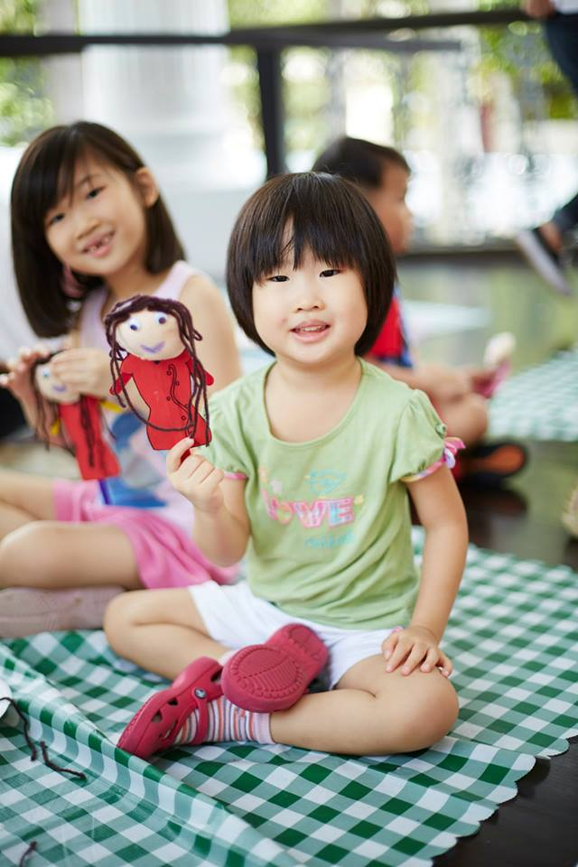 Girl holding up craft doll