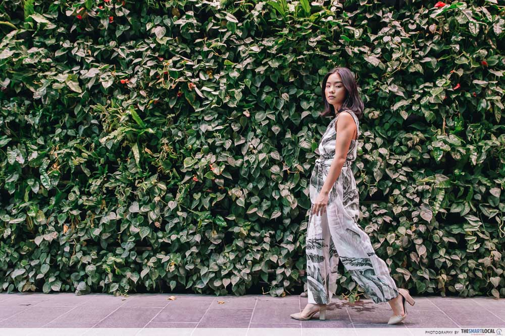 Girl walking by wall of greenery